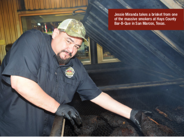 Jessie Miranda takes a brisket from one of the massive smokers at Hays County Bar-B-Que in San Marcos, Texas.